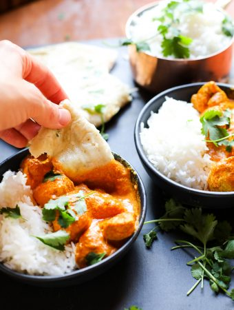 Naan dipped into butter chicken sauce